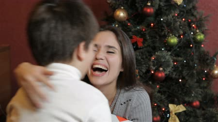 yanak : Young mother getting christmas gift from her little son. Little caucasian boy giving christmas gift to his mother against background of christmas tree. Pretty brunette woman thanks her son for the christmas gift by kissing his cheek Stok Video