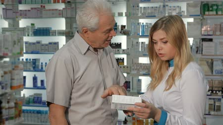фармацевт : Attractive female pharmacist telling male customer about some medicine. Pretty blond woman in medical uniform holding box of drugs at the drugstore. Senior male client asking young female druggist about medicine