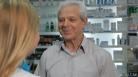 фармацевт : Blond female druggist giving customer a blister of red pills at the drugstore. Senior male client taking a blister of lozenges. Gray aged man showing blister of pills to the camera