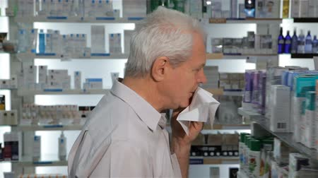 dispanser : Aged caucasian man coming to the drugstore with cough. Senior male client cover his mouth with handkerchief. Old gray caucasian man coughing near the displays at the pharmacy