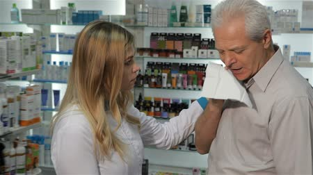 dispensary : Attractive female pharmacist offering lozenges for cough to the senior male customer. Pretty blond woman in medical uniform giving blister with lozenges to the aged caucasian man. Young female druggist putting her hand on the mans shoulder