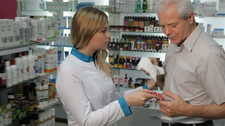 dispensary : Young female druggist giving client lozenges for cough at the pharmacy. Senior caucasian man taking blister of lozenges from the hands of pretty blond woman in medical uniform. Aged male customer and young female pharmacist looking at the camera