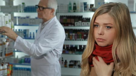 dispensary : Pretty blond woman caughing at the drugstore. Young caucasian woman in red big scarf needs remedy for caugh at the pharmacy. Attractive female customer standing against background of male pharmacist doing his job
