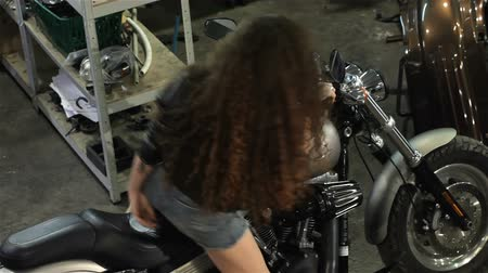 kudrnatý : Pretty female biker posing on the chopper at the mototrcycle workshop. High-angle shot of attractive caucasian girl sitting on the motorcycle. Sexy curly girl in black leather jacket and denim shorts putting her feet on the footrests of motorcycle