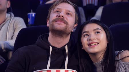 прижиматься : Close up of nice couple watching romantic film at the movie theater. Attractive caucasian boy snuggling with his girlfriend at the cinema. Pretty asian girl taking popcorn from bucket