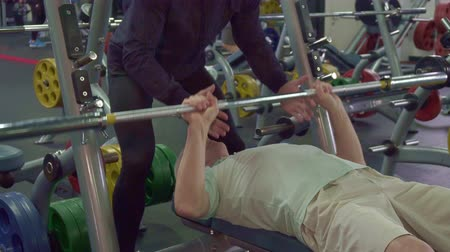 garça : Caucasian senior man training his chest muscles. Old gray sportsman pull up the bar on the bench. Close up of young male trainer ensuring his aged client at the gym Stock Footage