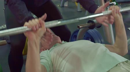 garça : Gray senior man pulling the bar from the chest. Young bearded guy holding his hands under the bar. Close up of aged male sportsman finishing his exercise