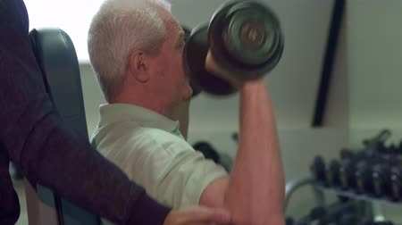 garça : Young caucasian trainer helping senior client during the training. Close up of bearded guy standing behind the old sportsman. Fit brunette man holding his hands under the elbows of aged man Stock Footage