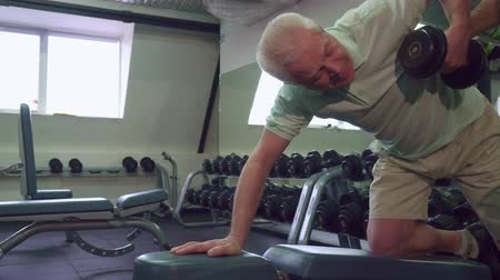 garça : Senior caucasian man pulling dumbbells up at the gym. Old gray sportsman holding his knee on the bench. Young trainer standing near his aged client