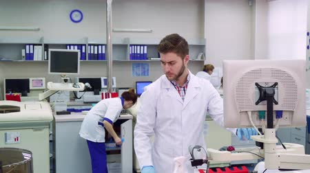 приехать : Young male scientist looking down at the laboratory. Attractive bearded man in white coat holding his hand near the computer. Caucasian guy working at the science lab Стоковые видеозаписи