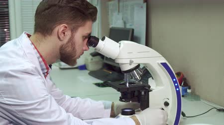 laboratorní plášť : Attractive young man in white coat looking through the scope at the laboratory. Side view of caucasian male scientist probing some testing material through the microscope. Brunette bearded lab worker holding his hand on coarse adjustment knob Dostupné videozáznamy