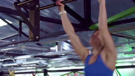 lift ups : Young sportswoman doing kipping pull ups at the gym. Slim female athlete hanging on the bar. Strong caucasian girl swinging before lifting her body