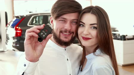 posando : Young caucasian man showing car key at the dealership. Close up of attractive couple posing against background of new black SUV. Handsome brunette man with car key in his hand and pretty brown haired girl smiling for the camera