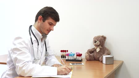 danışma : The doctor is sitting in his office. On the table is a teddy bear. The doctor writes something into a special notebook. Then he looks at the camera and smiles Stok Video