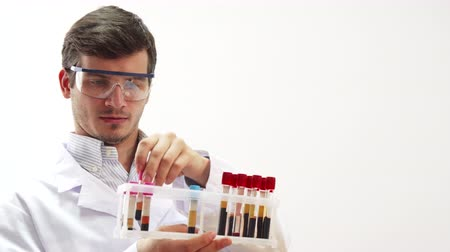 ajánlás : The doctor is in the laboratory. He wore special transparent glasses. He picks up a test tube with blood for medical tests. The doctor carefully studies it