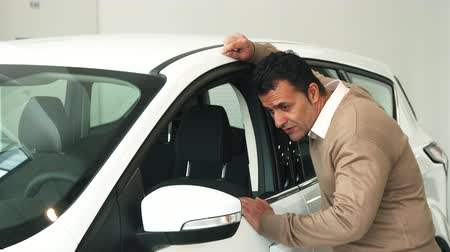 new clothes : A man comes to the open car window. He examines the interior of the car. Then he passes his hand over the rearview mirror. At the end the man looks at the camera and smiles Stock Footage