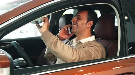 trousers : A man is sitting in the car. He is talking on his mobile phone. He also learns whats inside the car. The man looks very happy