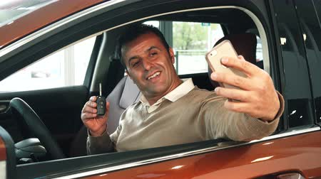 trousers : A man is sitting at the wheel of a car. He takes out the phone and the keys to the new car. Then he makes a selfie. He smiles very broadly
