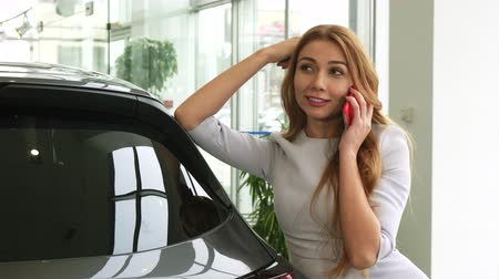 hívó : Attractive young red haired woman smiling happily talking on the phone while shopping for a new car at the dealership transport automotive industry buying consumerism communication.