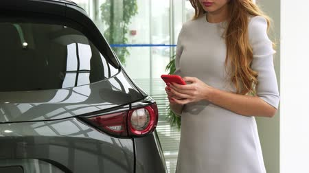 hívó : Cropped shot of a long haired woman standing near a new auto at the dealership using her smart phone typing messaging communication mobility consumerism driving buying.