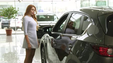 bérlet : Selective focus on a car lights gorgeous long haired woman choosing a new auto at the dealership consumerism shopping buying transport vehicle expensive retail offer sale discount purchase. Stock mozgókép