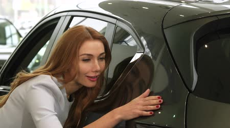 prawo jazdy : Close up of a stunning beautiful young woman smiling joyfully touching a car while shopping for a new auto at the dealership consumerism retail rental service emotions driving buying.