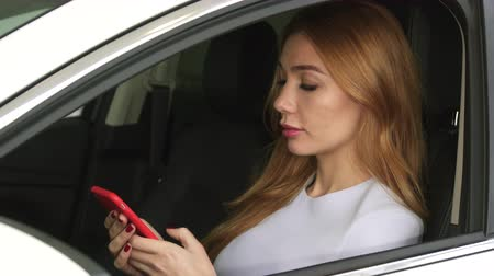 hívó : Attractive young sexy woman using smart phone sitting in her car smiling to the camera technology communication safety driving online automotive rental service connection mobility travelling.
