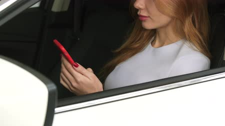 hívó : Cropped close up of a female driver sitting in a car smiling using smart phone communication internet online wireless carrier safety owner travel navigation technology mobility. Stock mozgókép