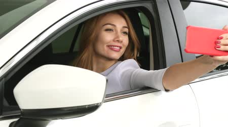 hívó : Cheerful young beautiful long haired woman sitting in a new car using smart phone taking selfies smiling joyfully emotions happiness driving travelling consumerism technology social