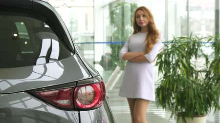 loans : Selective focus on car lights gorgeous sexy woman in a dress looking at the auto thoughtfully decising which automobile to buy consumerism client customer purchasing sales rental retail.