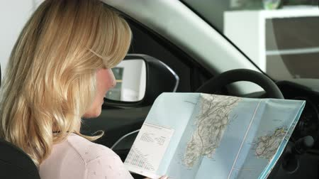 prawo jazdy : Close up of a gorgeous blonde mature woman smiling to the camera cheerfully after searching directions on a map sitting in a car travelling destination driving navigation transport auto. Wideo