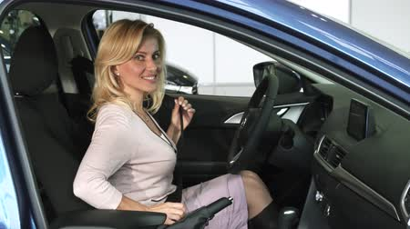 loans : Stunning mature woman smiling to the camera fastening seatbelt sitting behind the steering wheel in a new auto at the dealership customer buyer buying sales retail rental consumerism.