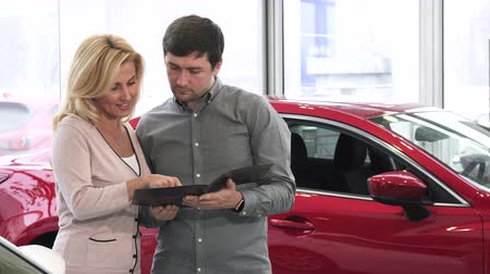 буклет : Happy mature couple choosing a new car to buy husband and wife reading booklet at the dealership salon consumerism buying automotive retail rental choice purchase travel driving.