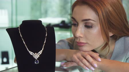 pingente : Close up of a beautiful sad woman looking unhappy and disappointed posing with an expensive diamond necklace not able to afford the purchase jewelry store buying money credit loan.