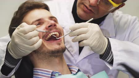 examinando : Cropped close up of a handsome young man having his teeth examined by a professional dentist at the clinic medicine health clinical appointment patient dentistry trust occupation service. Vídeos