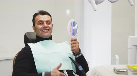 painless : Cheerful handsome mature male patient sitting in the dental chair looking in the mirror smiling showing thumbs up curing cavity treatment health medicine dentistry clinical examination.