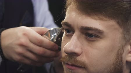 barbering : Cropped close up of a young handsome man looking away while professional barber giving him a new haircut masculinity lifestyle fashion service professionalism client customer barbering.