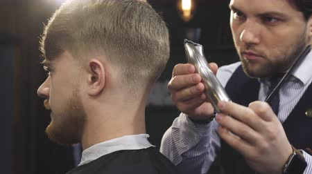 wąsy : Cropped close up of a handsome professional barber working at his barbership using electrical clipper or trimmer styling hair of his male client service occuaption profession job worker masculine.