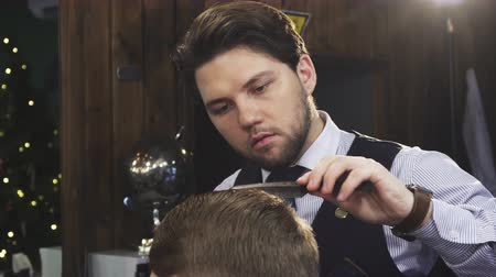barbering : Close up of a handsome bearded professional baber working styling hair of his male client spraying it with water combing profession job occupation barbershop barbering skills stylist masculine.