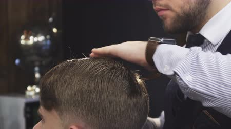 barbering : Cropped clsoe up of a professional barber spraying water on the hair of his client while styling it profession job career occupation entrepreneurship lifestyle traditional barbering barbershop. Stock Footage