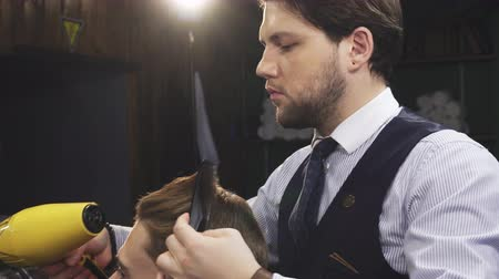 barbering : Handsome young professional barber working at his barbershop drying hair of his client with a blow dryer occupation job professionalism styling stylist barbering equipment haircare. Stock Footage