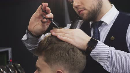 barbering : Cropped clsoe up of a professional barber working at the barbership using scissors and comb cutting hair of his client consumerism barbering service occupation job styling profession.