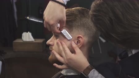 barbering : Close up of a young handsome bearded man getting shaved by a professional barber using razor working at the barbershop grooming styling hairstyle profession service occupation barbering. Stock Footage