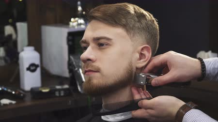 barbering : Close up of a handsome young man smiling while professional barber trimming his beard with a clipper trimmer equipment service consumerism masculinity beardcut barbering barbershop lifestyle.