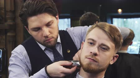 barbering : Professional barber working at his barbershop trimming beard of his male handsome client occupation profession job service barbering consumerism styling beardcut. Stock Footage