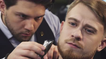 bigode : Sliding close up shot of a handsome young man getting his beard trimmed by a professional barber at the barbershop barbering styling profession occupation service lifestyle. Stock Footage