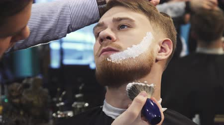 barbering : Handsome young man getting his beard shaved at the barbershop professional barber applying shaving cream on his face and neck beardcut barbering service customer fashion professional.