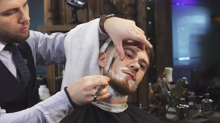barbering : Close up of a handsome young man getting his beard shaved at the barbershop professional barber using a razor shaving his client profession occupation service job barbering styling. Stock Footage
