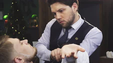 barbering : Professional barber working at his barbershop shaving his young male client with a razor careful dangerous professionalism experience skills barbering styling beard.