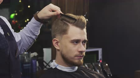 barbering : Close up of a handsome young man getting his hair styled by a professional barber using hairspray and blowdryer professionalism barbering barbershop style fashion masculinity tradition.